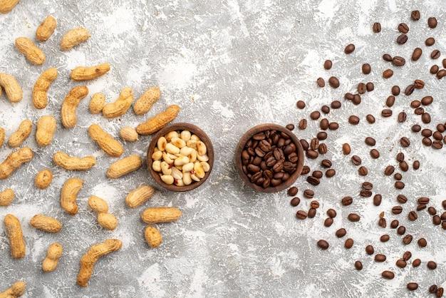 Draufsicht auf leckere erdnüsse mit braunen kaffeesamen auf weißer oberfläche