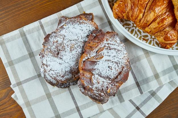 Draufsicht auf leckere frisch gebackene schokoladencroissants auf beigem stoff auf einem holztisch. lebensmittelfotografie für bäckerei-cafés. nahaufnahme.