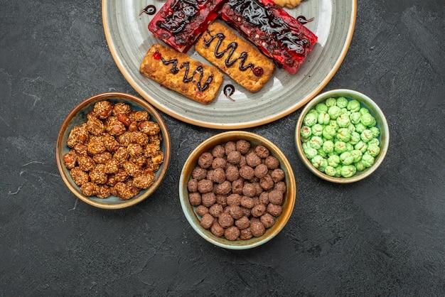 Draufsicht auf leckere fruchtige kuchen mit keksen und bonbons im dunkeln