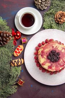 Draufsicht auf leckere fruchtige pfannkuchen mit tasse tee im dunkeln