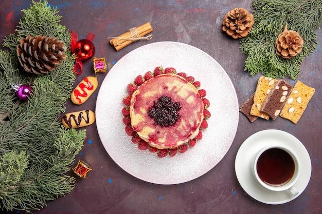Draufsicht auf leckere geleepfannkuchen mit erdbeeren und tasse tee im dunkeln