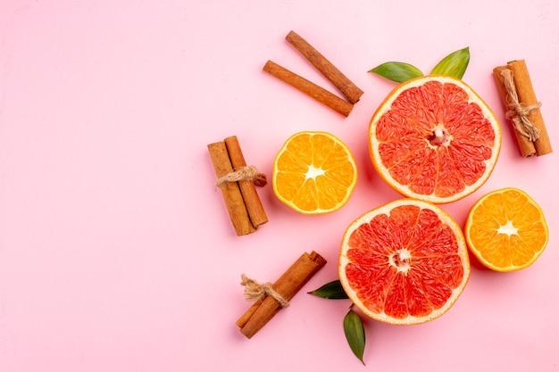 Draufsicht auf leckere grapefruits-fruchtscheiben mit zimt auf der rosa oberfläche