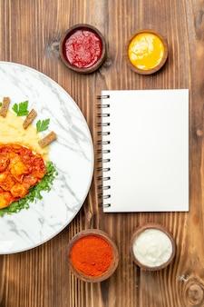 Draufsicht auf leckere hähnchenscheiben mit gewürzen und kartoffelpüree auf braunem tisch. gericht pfeffer fleisch mahlzeit abendessen