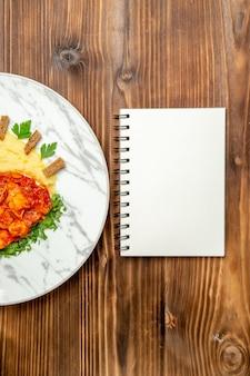 Draufsicht auf leckere hähnchenscheiben mit kartoffelpüree auf braunem tisch.