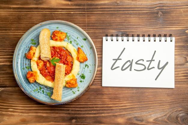 Draufsicht auf leckere hähnchenscheiben mit kartoffelpüree und leckerem wort auf braunem tisch. gericht pfeffer fleisch mahlzeit abendessen