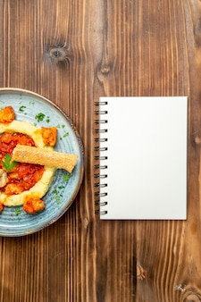 Draufsicht auf leckere hähnchenscheiben mit kartoffelpüree und notizblock auf braunem tisch. gericht pfeffer fleisch mahlzeit abendessen