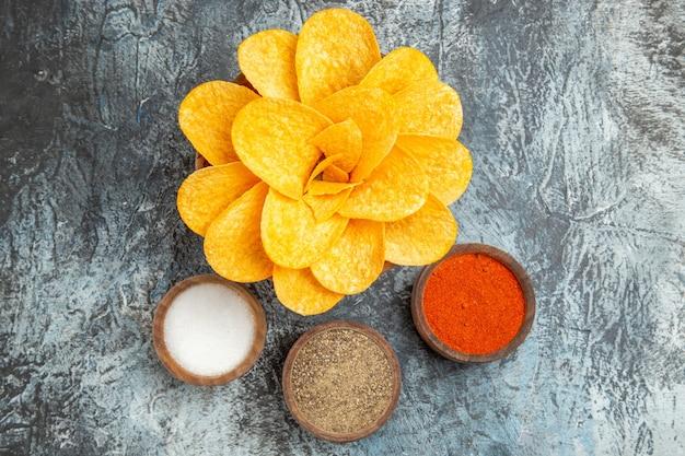 Draufsicht auf leckere kartoffelchips, die wie blumen und verschiedene gewürze auf grauem tisch verziert sind