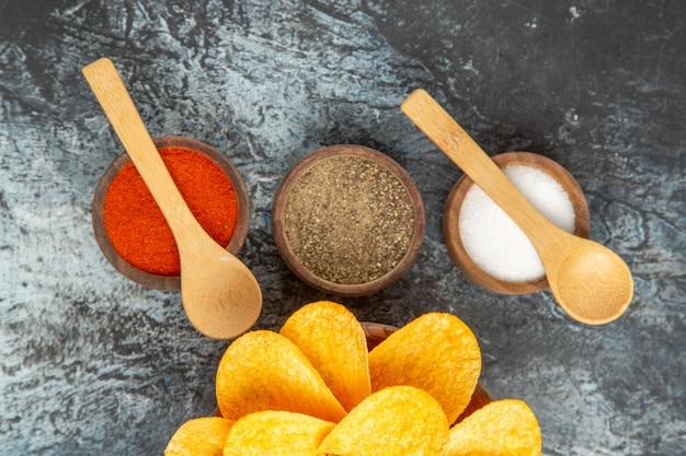 Draufsicht auf leckere kartoffelchips, die wie blumenförmige verschiedene gewürze mit löffeln auf grauem tisch verziert sind
