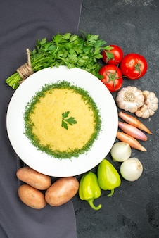 Draufsicht auf leckere kartoffelpüree mit grün und frischem gemüse auf schwarzem tisch