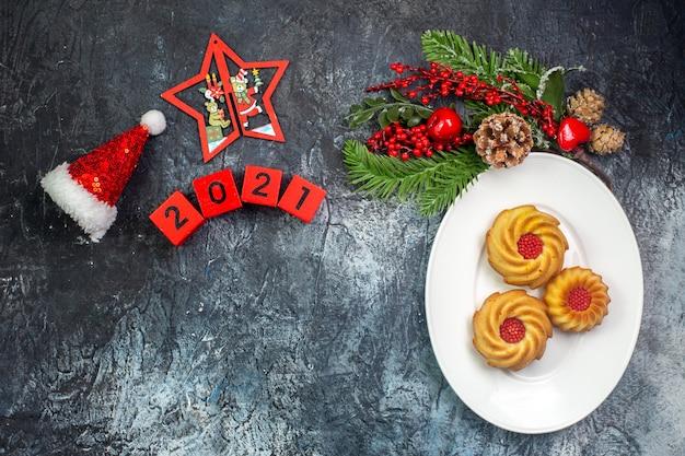 Draufsicht auf leckere kekse auf einem weißen teller und neujahrsdekorationen weihnachtsmann-hut neben zahlen auf dunkler oberfläche