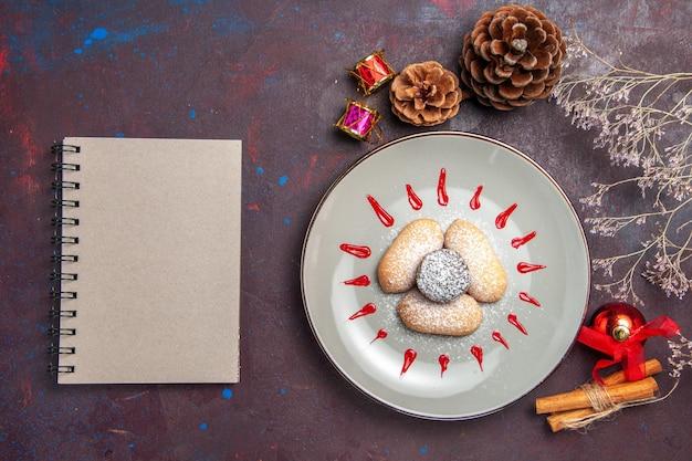 Draufsicht auf leckere kekse mit rotem zuckerguss auf schwarz