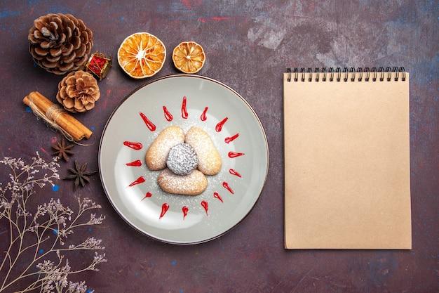 Draufsicht auf leckere kekse mit rotem zuckerguss im teller auf schwarz