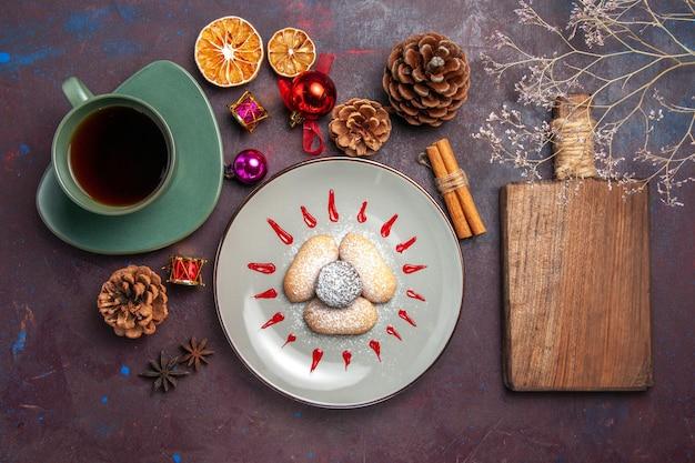 Draufsicht auf leckere kekse mit tasse tee auf schwarz