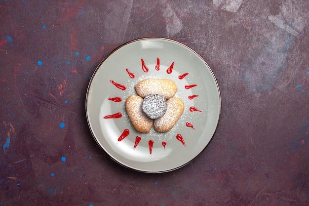Draufsicht auf leckere kekse mit zuckerpulver und rotem zuckerguss auf der innenseite des tellers auf dunkel