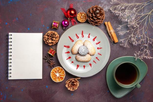Draufsicht auf leckere kekse mit zuckerpulverbonbons mit einer tasse tee auf schwarz on