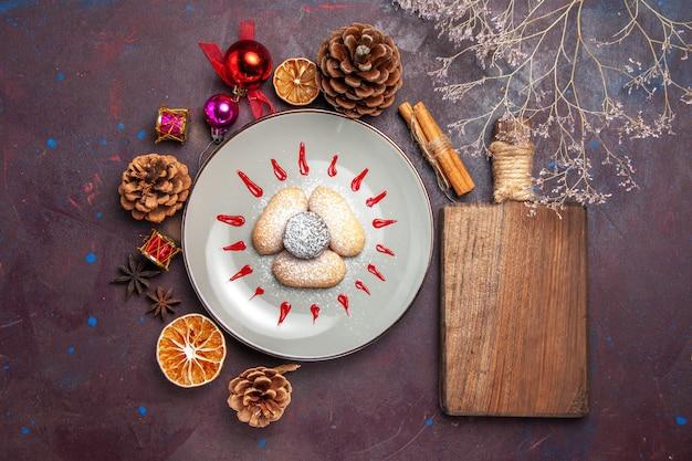Draufsicht auf leckere kekse, zuckerpulverbonbons auf schwarz on