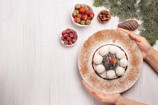Draufsicht auf leckere kokosbonbons mit kakaokuchen auf weiß