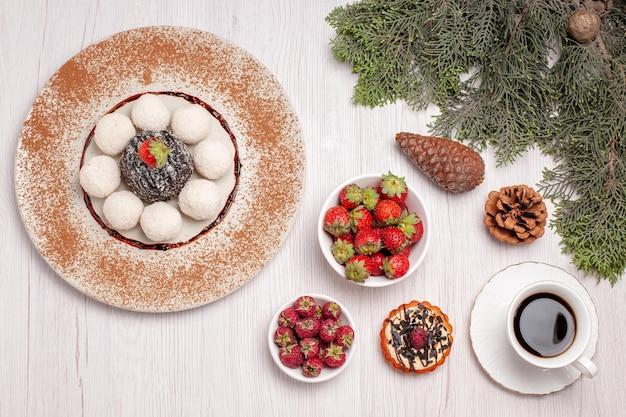 Draufsicht auf leckere kokosbonbons mit kuchentee und früchten auf weiß