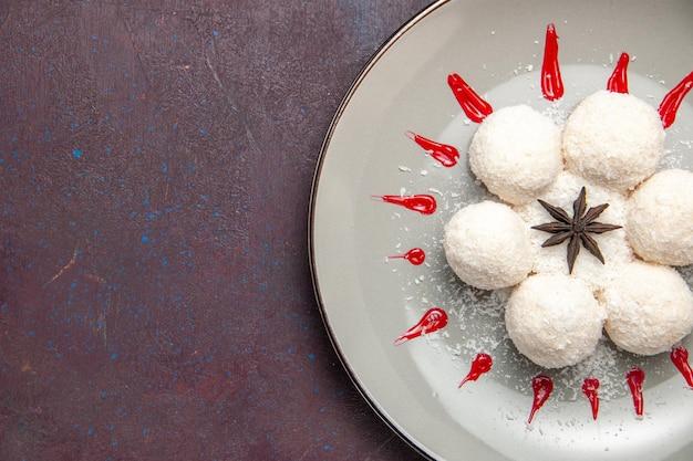 Draufsicht auf leckere kokosbonbons mit rotem zuckerguss auf schwarzem tisch