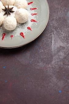 Draufsicht auf leckere kokosbonbons rund geformt mit rotem zuckerguss auf schwarz