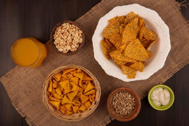 Draufsicht auf leckere kornförmige gebratene maissnacks auf einem eimer auf einem sack mit pinienkernen auf einer holzschale mit geschälten sonnenblumenkernen mit einem glas orangensaft auf einem holztisch