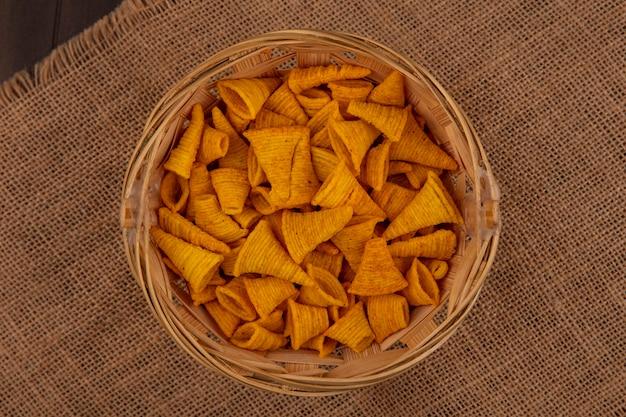Draufsicht auf leckere kornförmige gebratene maissnacks auf einem eimer auf einem sackstoff auf einem holztisch