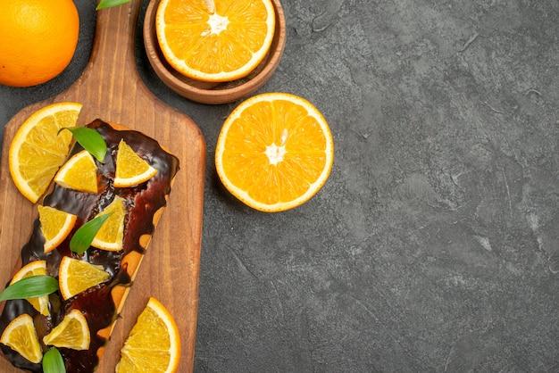 Draufsicht auf leckere kuchen ganz und geschnittene orangen auf schneidebrett auf schwarzem tisch