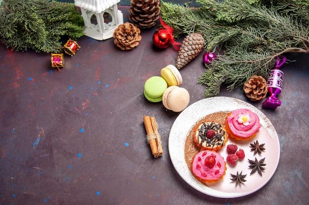 Draufsicht auf leckere kuchen mit französischen macarons auf schwarz