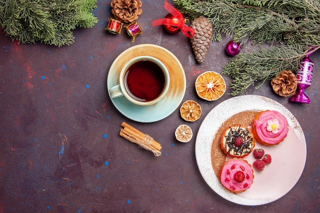 Draufsicht auf leckere kuchen mit tasse tee auf schwarz