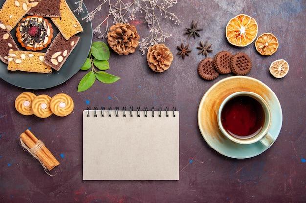 Draufsicht auf leckere kuchenscheiben mit einer tasse tee auf schwarz