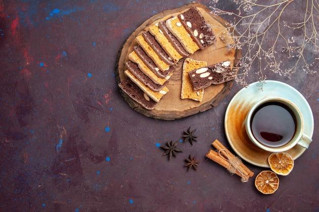 Draufsicht auf leckere kuchenscheiben mit nüssen und tee auf schwarz