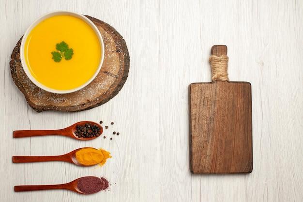 Draufsicht auf leckere kürbissuppe mit pfeffer auf weiß
