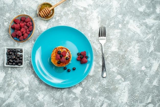 Draufsicht auf leckere muffins mit beeren und honig auf heller oberfläche