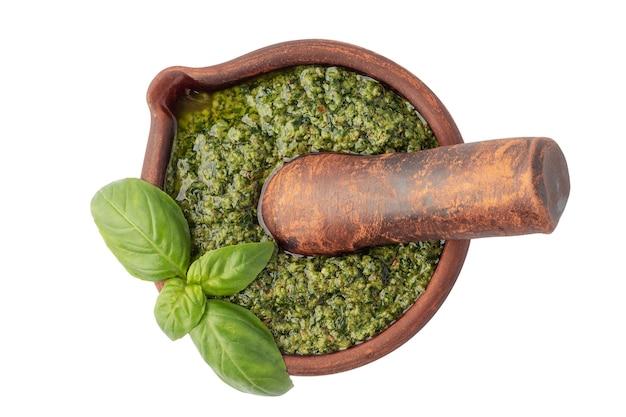 Draufsicht auf leckere pesto-sauce in tonmörser mit stößel auf weißem hintergrund