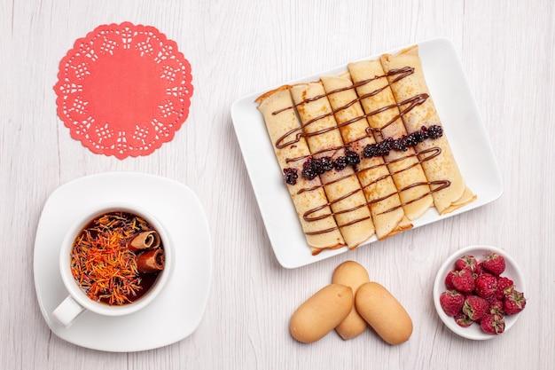 Draufsicht auf leckere pfannkuchenröllchen mit tasse tee auf weiß