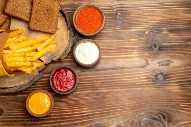 Draufsicht auf leckere pommes frites mit gewürzen auf braunem tisch