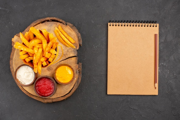 Draufsicht auf leckere pommes frites mit saucen auf schwarz