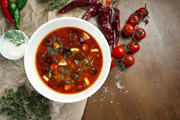 Draufsicht auf leckere solyanka dicke, würzige und saure russische suppe mit oliven, zitrone und würstchen in weißer schüssel auf holzoberfläche.
