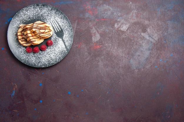 Draufsicht auf leckere süße brötchen in scheiben geschnittenen kuchen für tee im teller auf schwarz