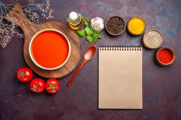 Draufsicht auf leckere tomatensuppe mit gewürzen und frischen tomaten auf dunkelheit tomatoes