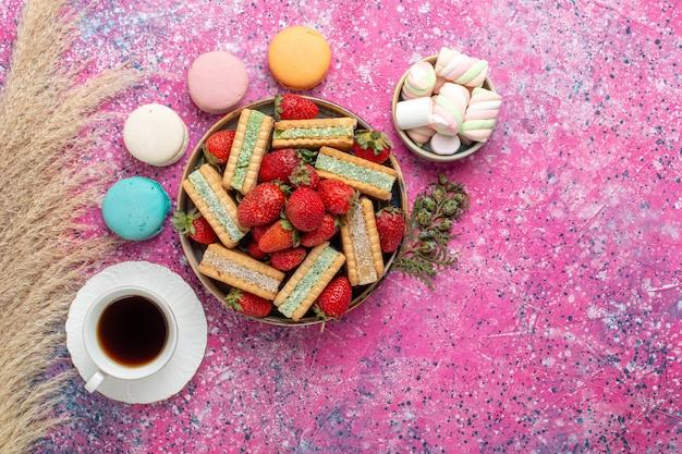 Draufsicht auf leckere waffelkekse mit frischen roten erdbeer-macarons und tee auf rosa oberfläche
