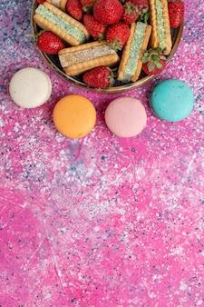 Draufsicht auf leckere waffelkekse mit macarons und frischen roten erdbeeren auf rosa oberfläche