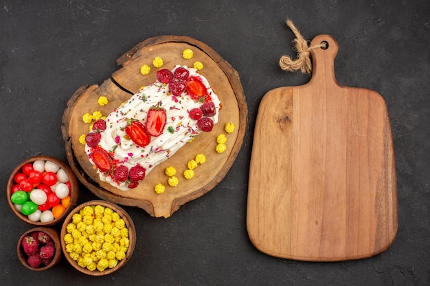 Draufsicht auf leckeren cremigen kuchen mit früchten und süßigkeiten auf schwarzem tisch black