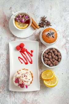 Draufsicht auf leckeren cremigen kuchen mit tasse tee und zitronenscheiben auf weiß on