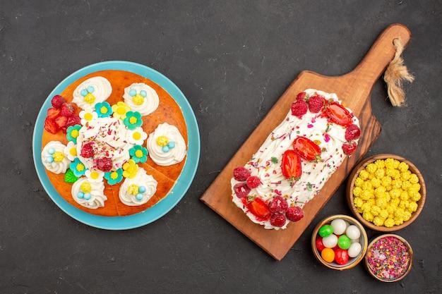 Draufsicht auf leckeren fruchtigen kuchen mit bonbons und torte auf schwarz