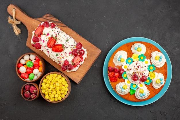 Draufsicht auf leckeren obstkuchen mit süßigkeiten und kuchen auf schwarz