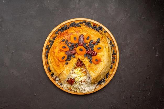 Draufsicht auf leckeren shakh plov mit rosinen und getrockneten aprikosen auf der dunklen oberfläche