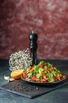 Draufsicht auf leckeren veganen salat mit frischen zutaten in einem teller und gabel auf schwarzem schneidebrett