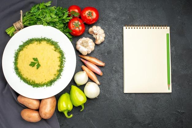 Draufsicht auf leckeres kartoffelpüree mit grün und frischem gemüse auf schwarz