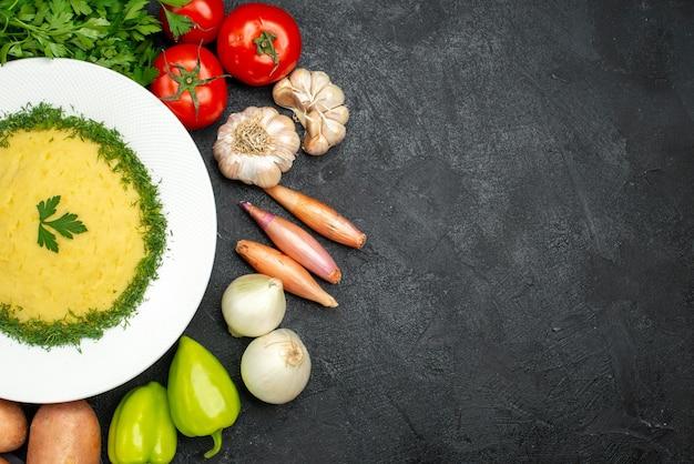 Draufsicht auf leckeres kartoffelpüree mit grün und frischem gemüse auf schwarzem grau